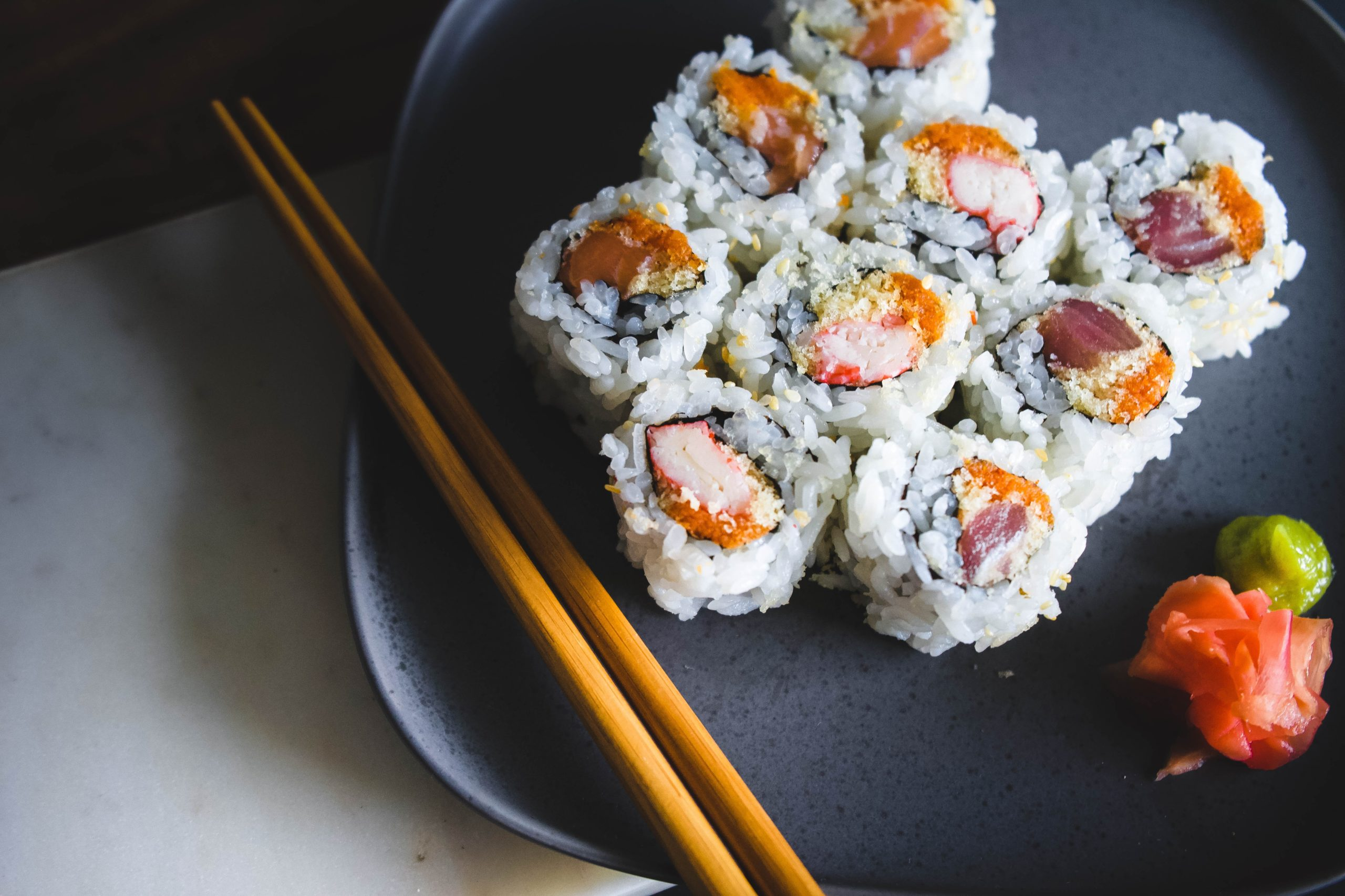 A spicy tuna sushi roll on a plate with chopsticks.