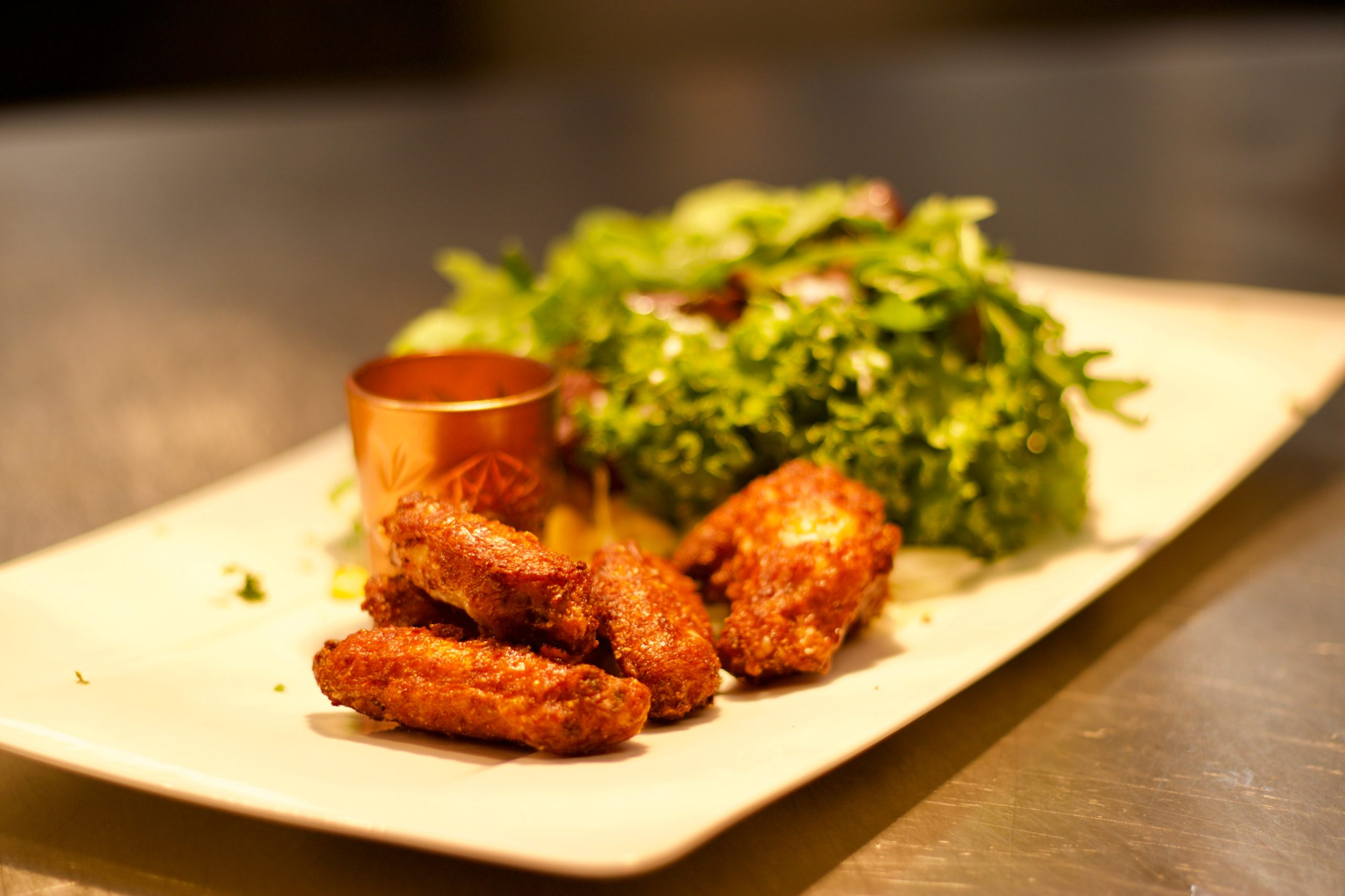 Koren fried chicken wings on a plate with dipping sauce and leafy vegetables.