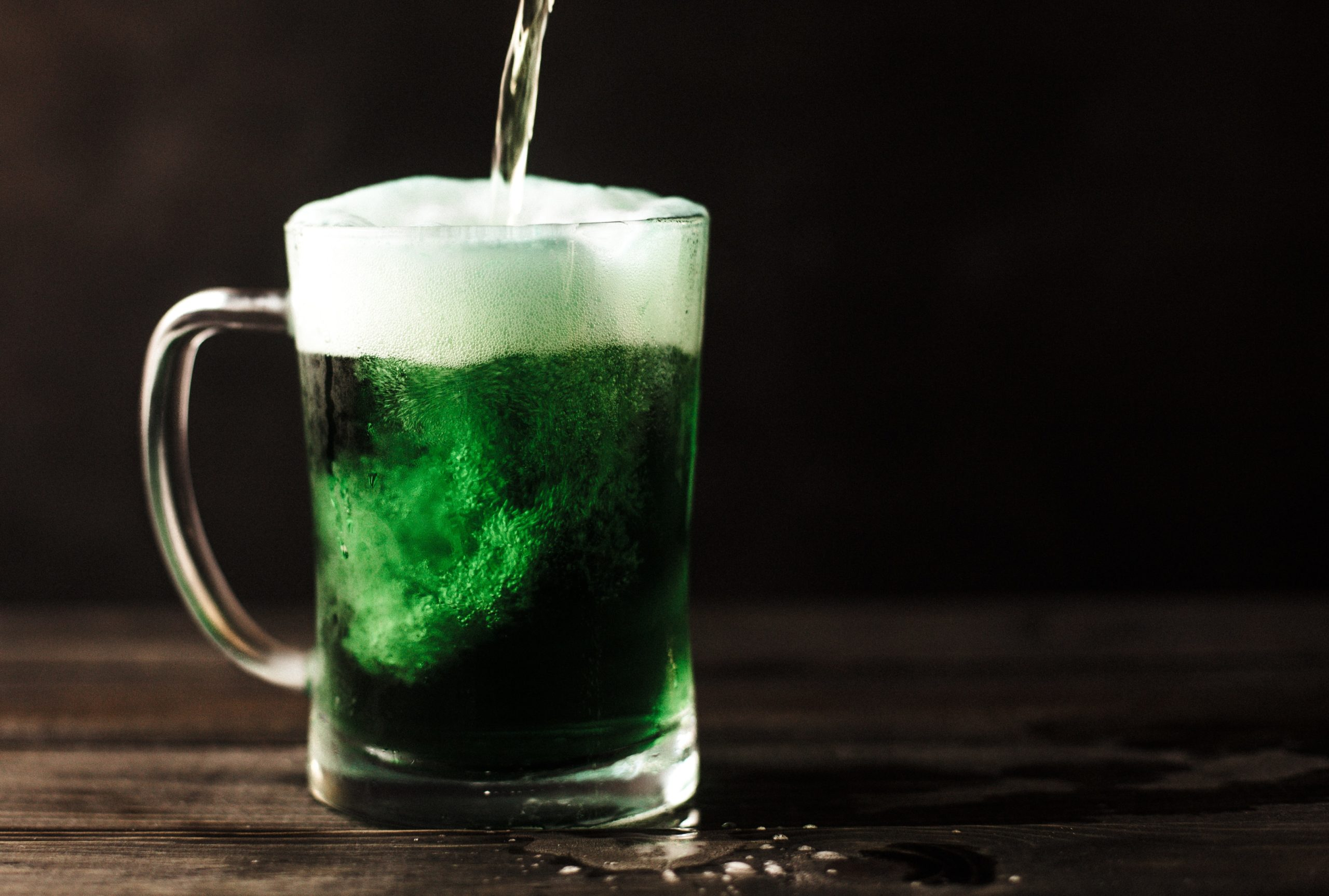 A mug of green beer being poured.