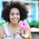 woman eating pink donut from donut shops in Germantown