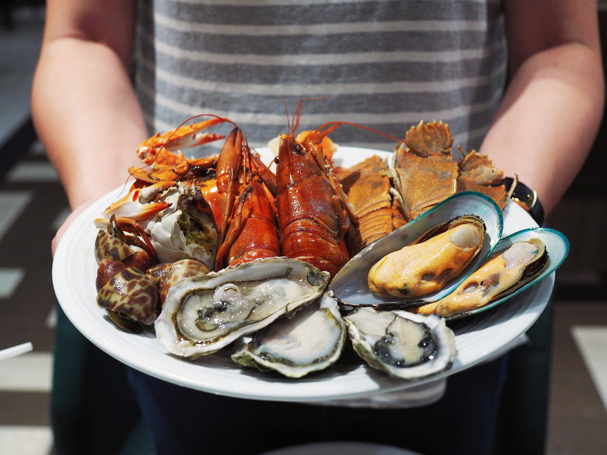someone carrying a plate of seafood.