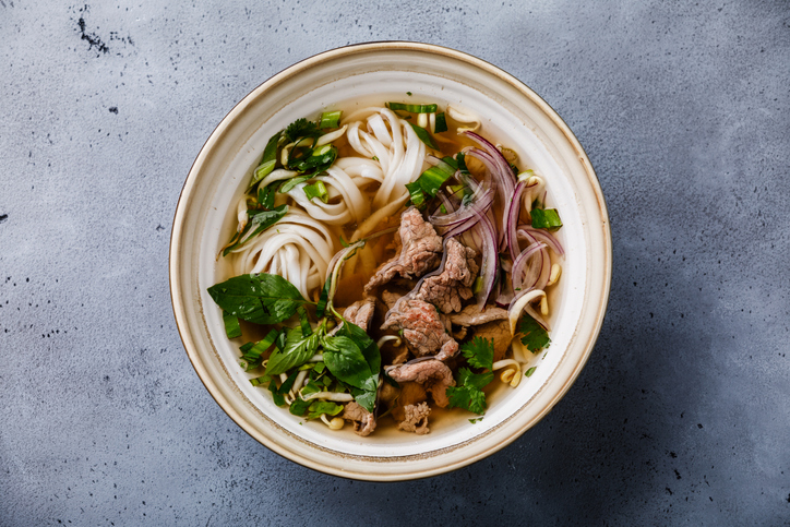A bowl of pho on a table.