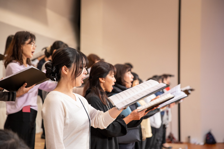 A group of choir singers practicing in a music room.