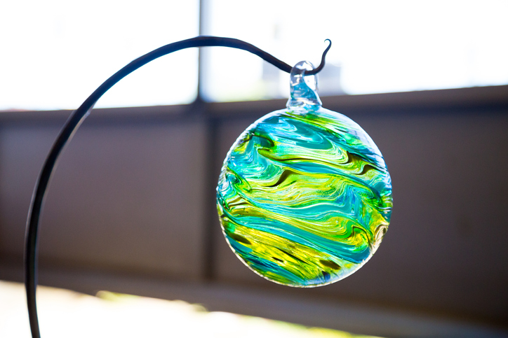 A glassblown ornament hanging on a stand - Germantown glassblowing studios