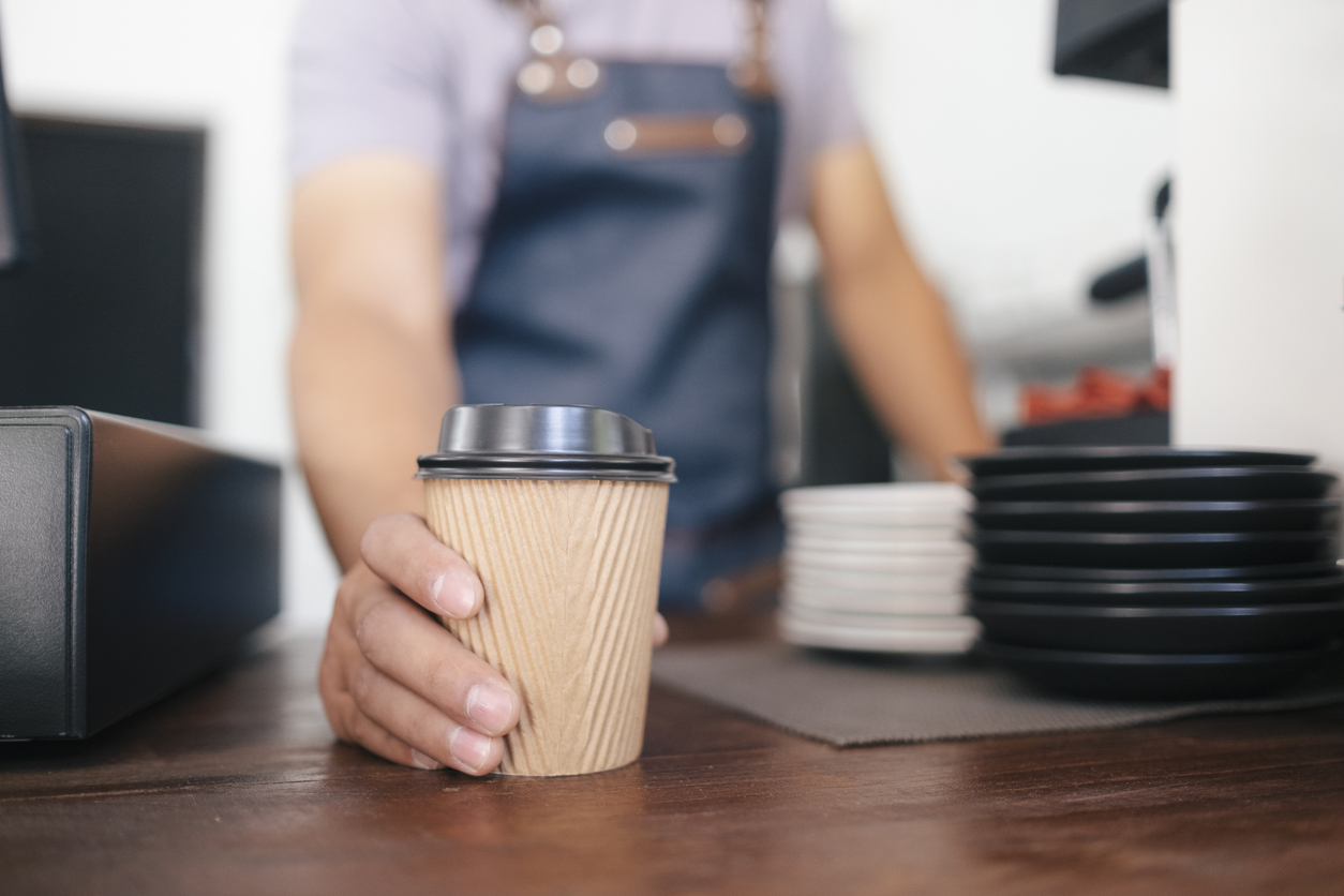 Barista placing a cup of coffee on the pickup counter at a coffee shop around Germantown